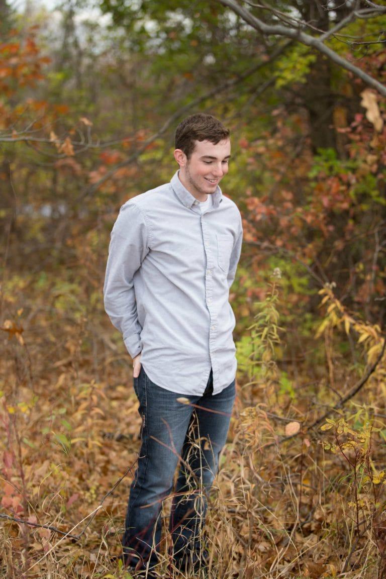 Senior Guy poses in fall foliage