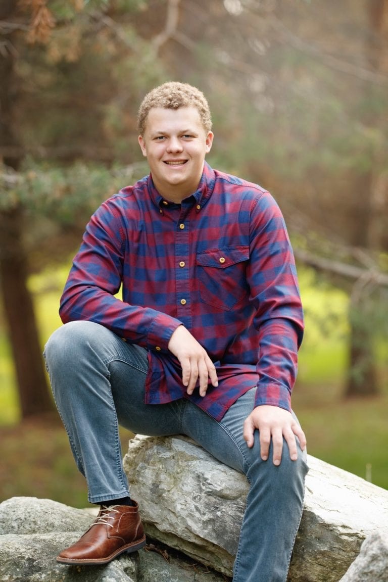 Senior guy sitting on rocks