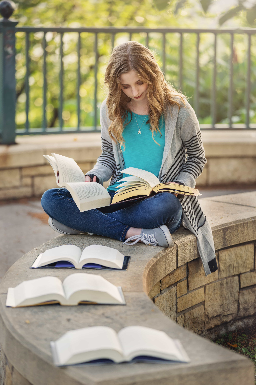 Senior girl reading multiple books at once outside in a park.