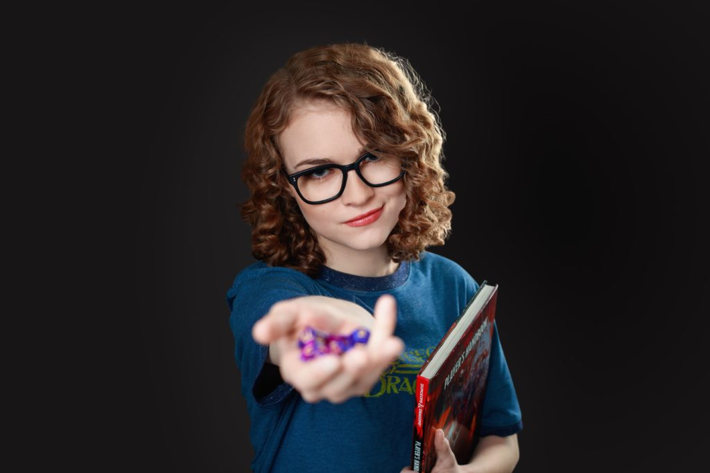 Senior girl with dungeons and dragons game in the studio.