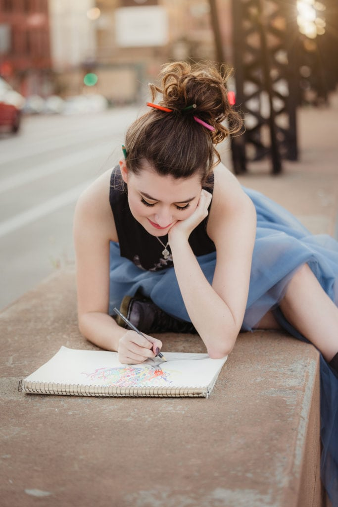 Senior girl drawing on a sketchpad downtown.