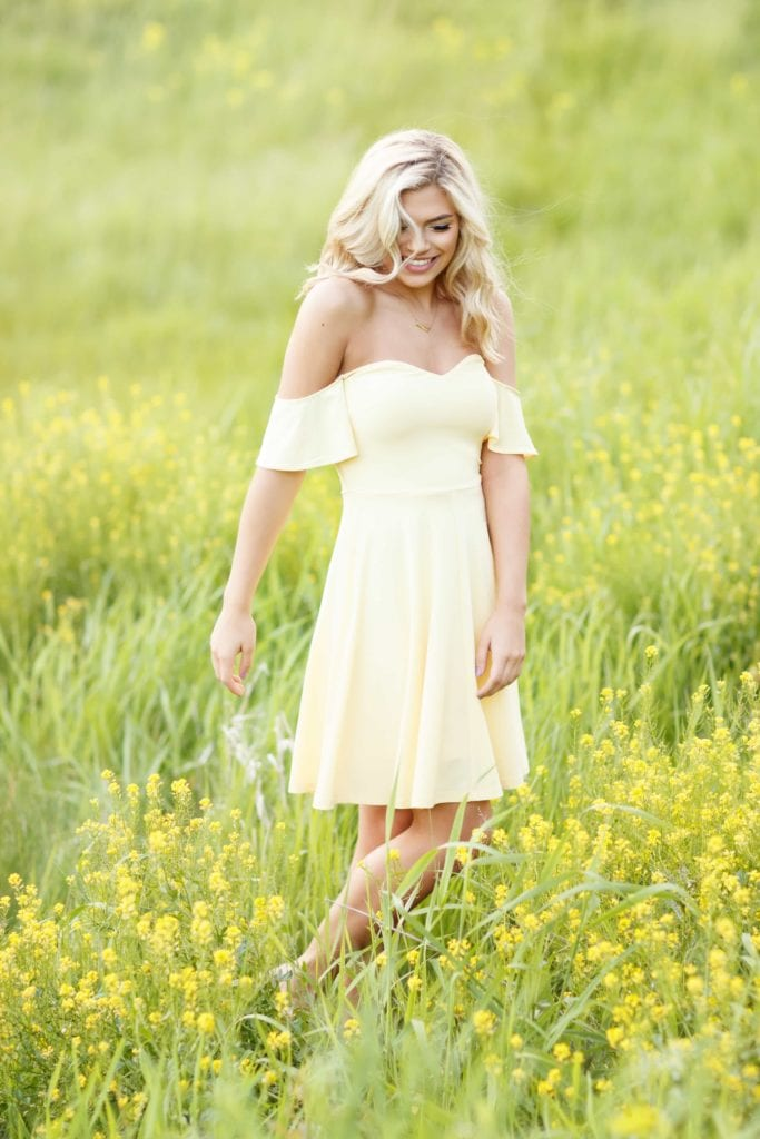 Senior girl poses with flowers in a field