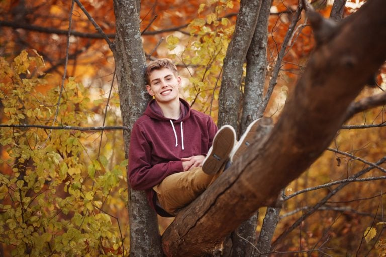 Senior guy sits in a tree near Maple Grove, Minnesota