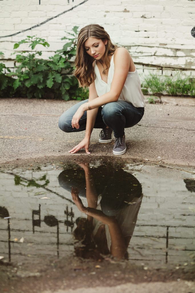 Senior girl lookin at her reflection in a puddle.