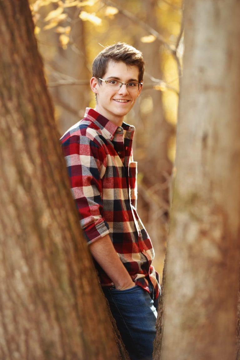 Senior guy looking between the trees