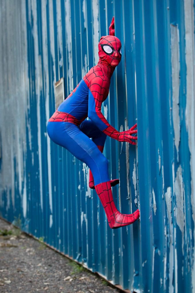 Senior guy in a spiderman costume climbing a wall.