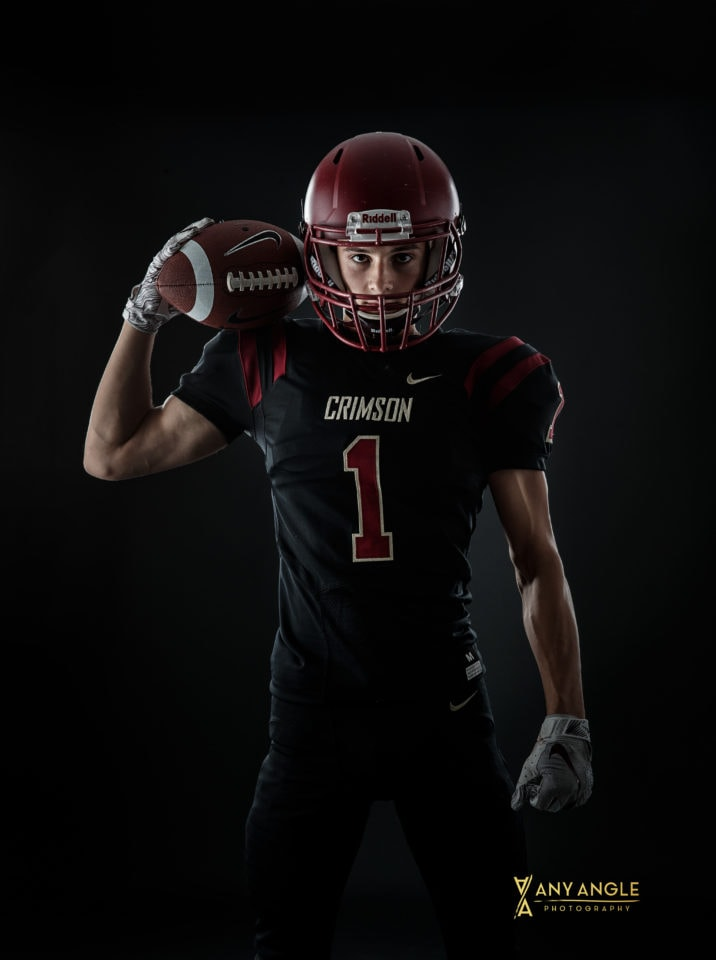 Senior guy pictures of football player in studio with dark background