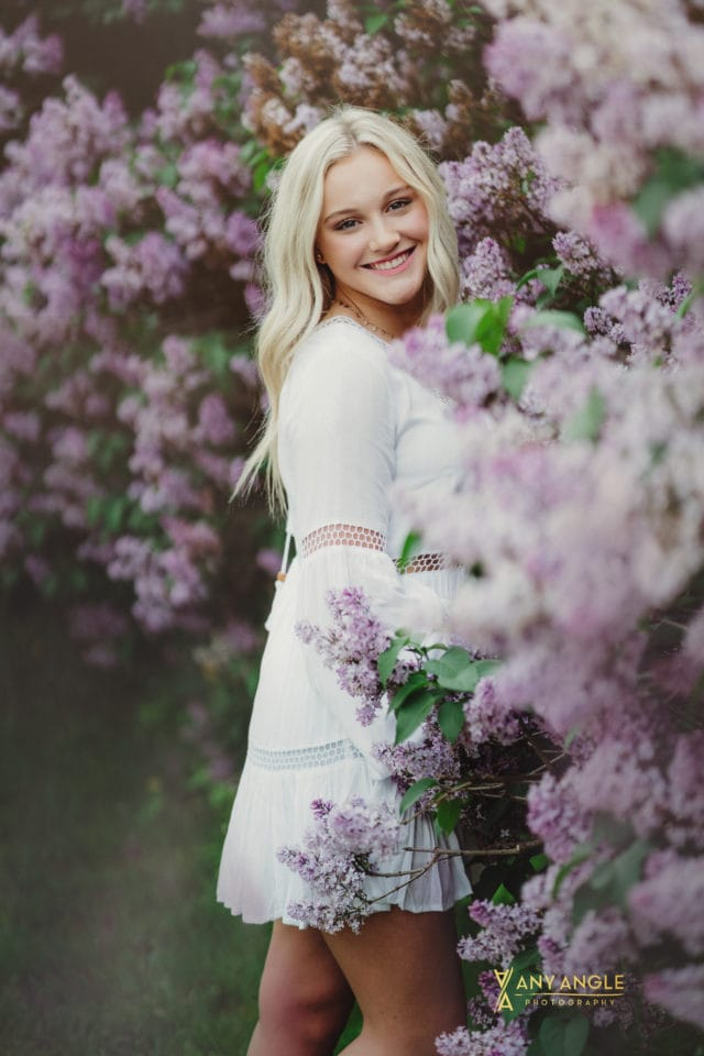 spring high school blonde senior in white dress standing in lilac bushes Any Angle Photography