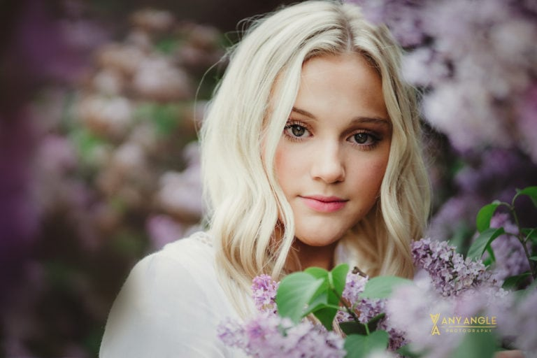 spring high school senior girl in white dress in lilac bushes
