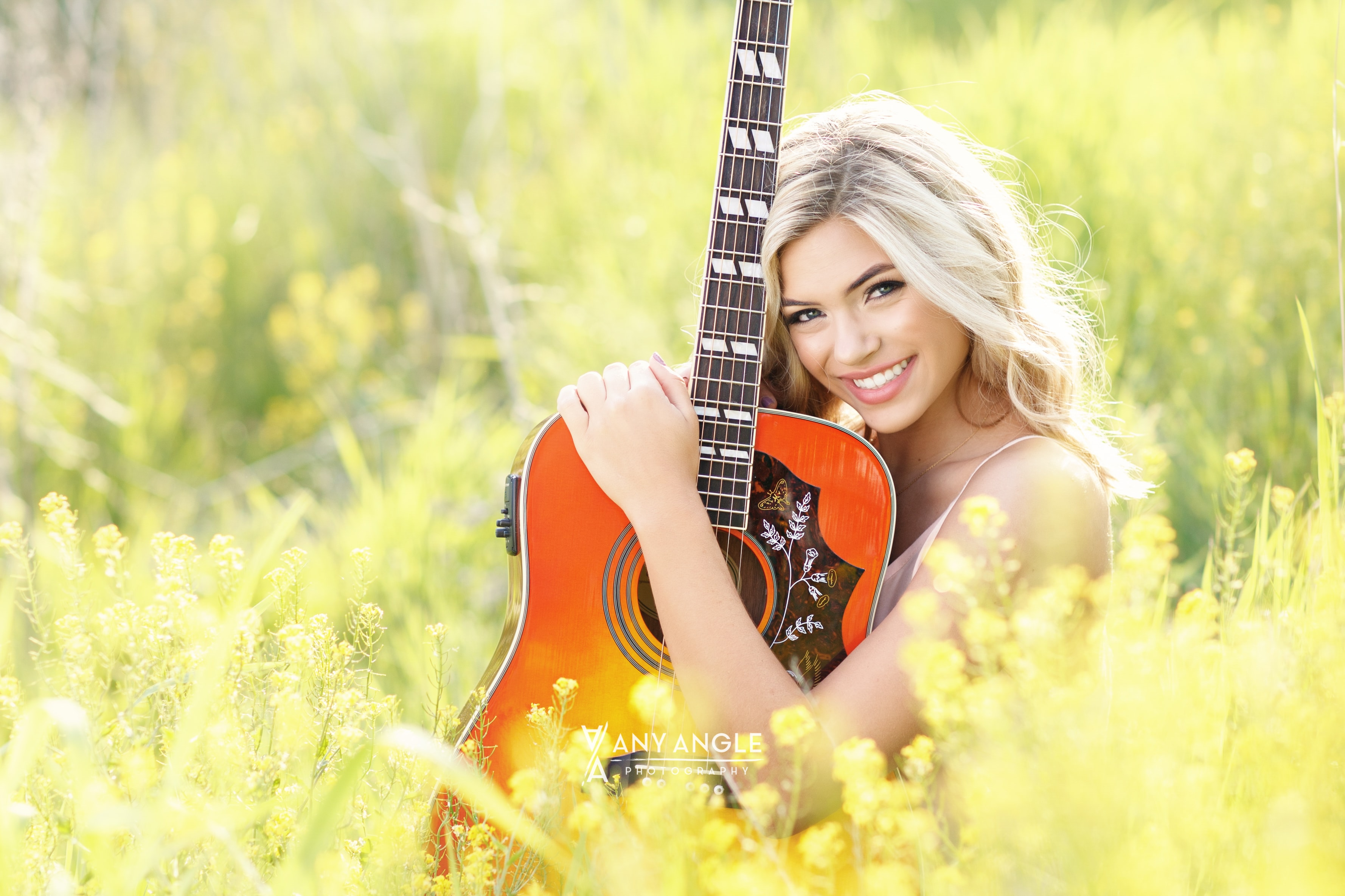 Spring senior pictures of girl in a field with guitar