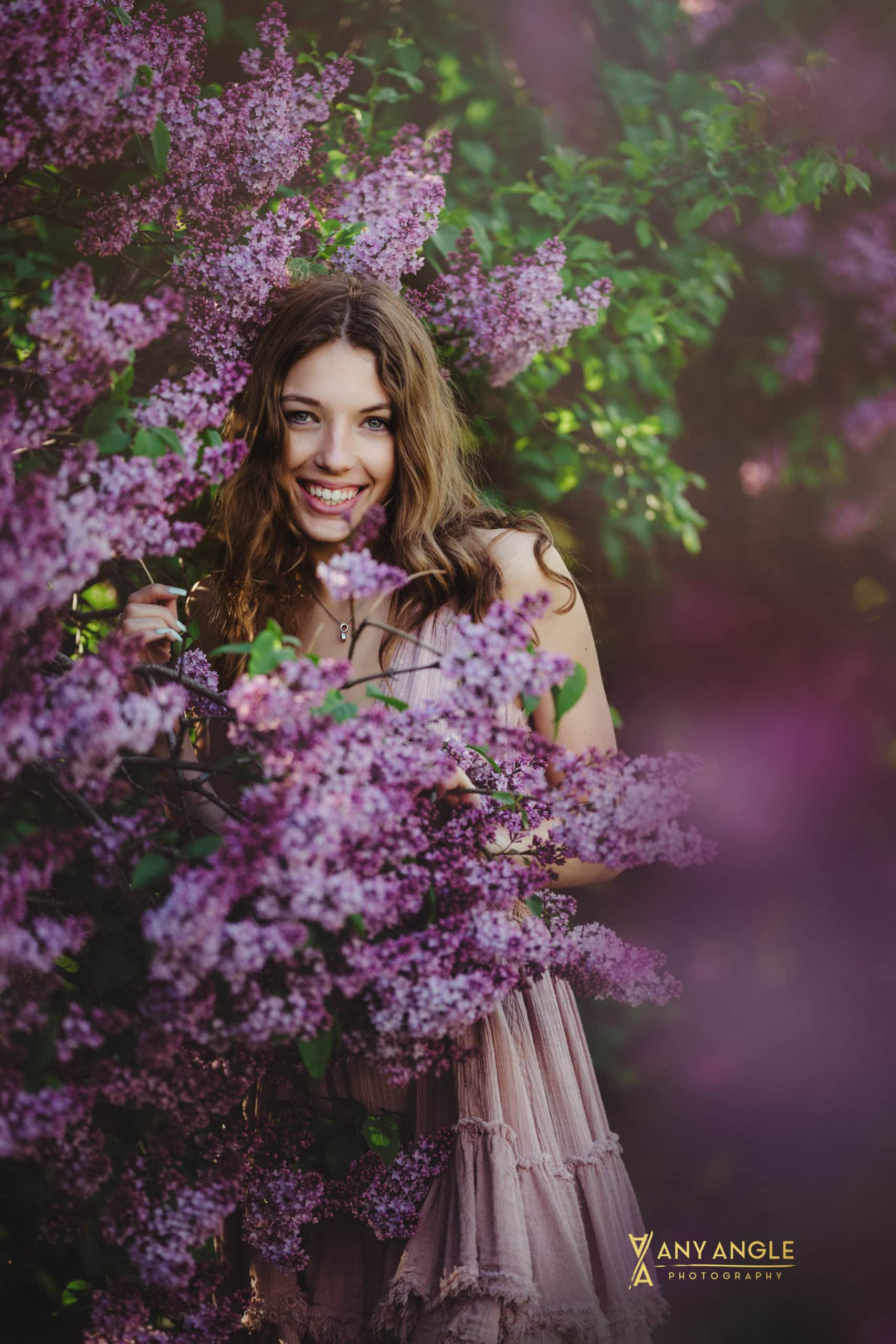 spring senior pictures with girl  in pink dress standing underneath lilac bush covered with purple blossoms