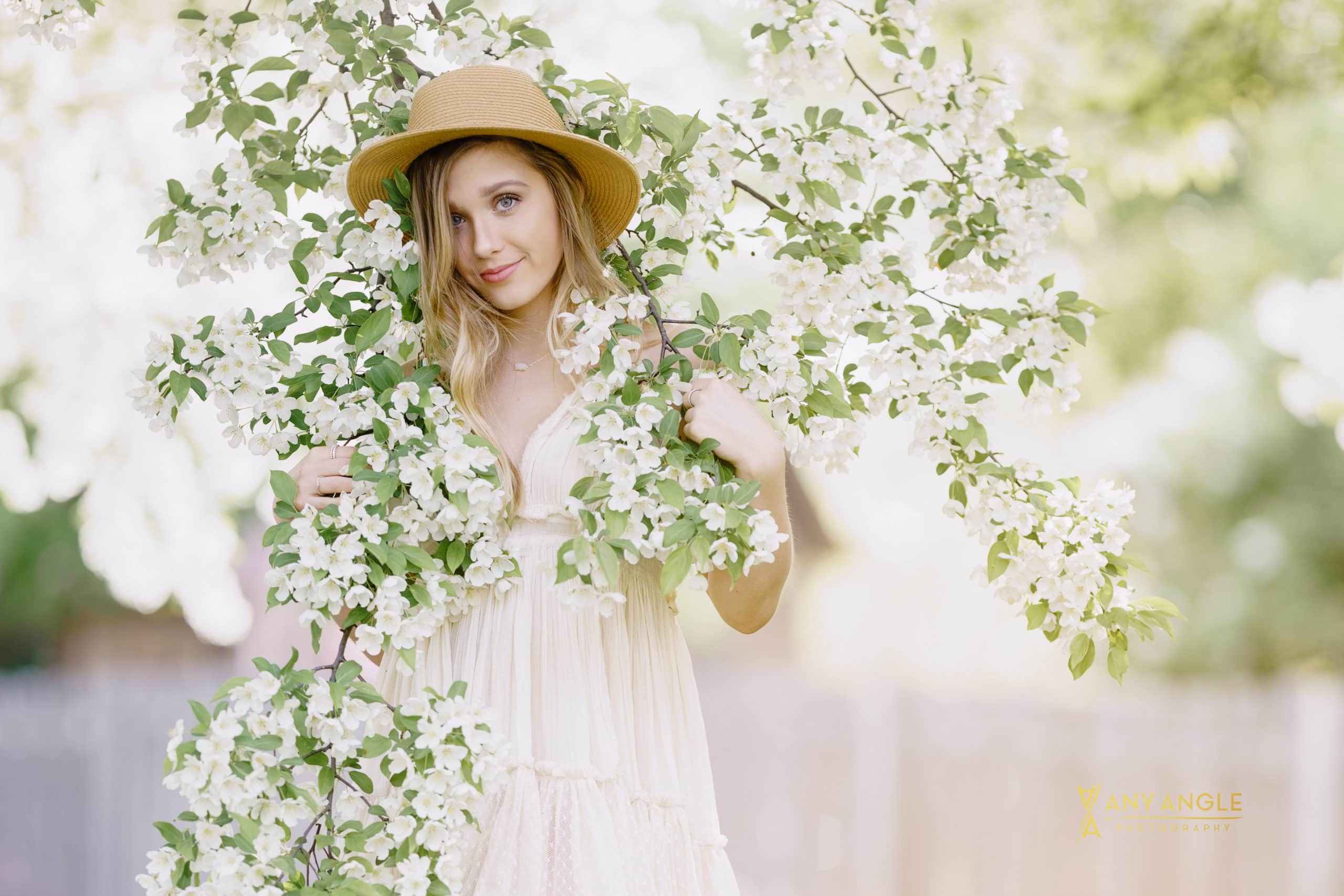 spring senior pictures with girl  in white dress standing underneath tree  covered with white blossoms
