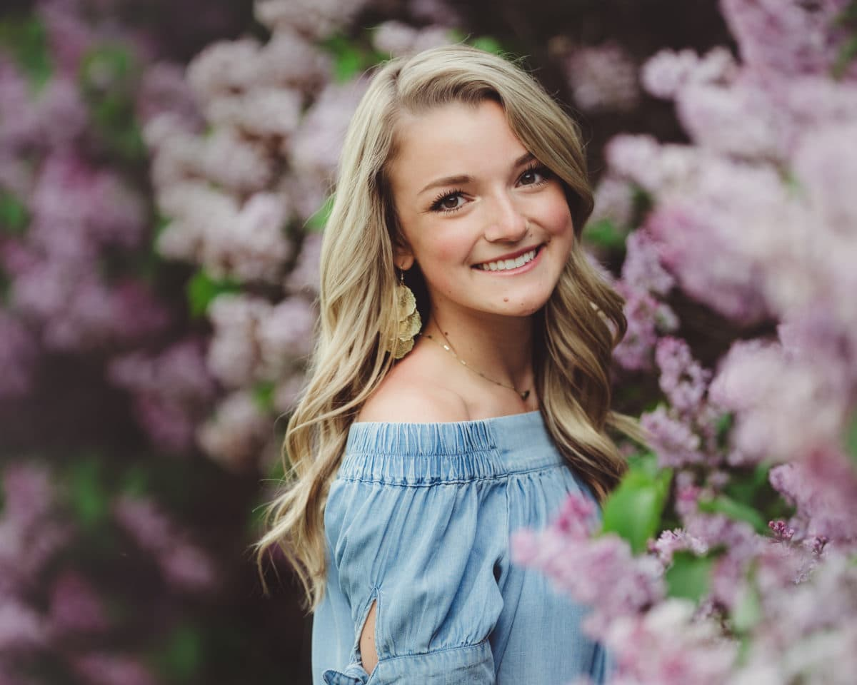 high school senior girl in blue dress standing in from of purple lilac bushes smiling at camera