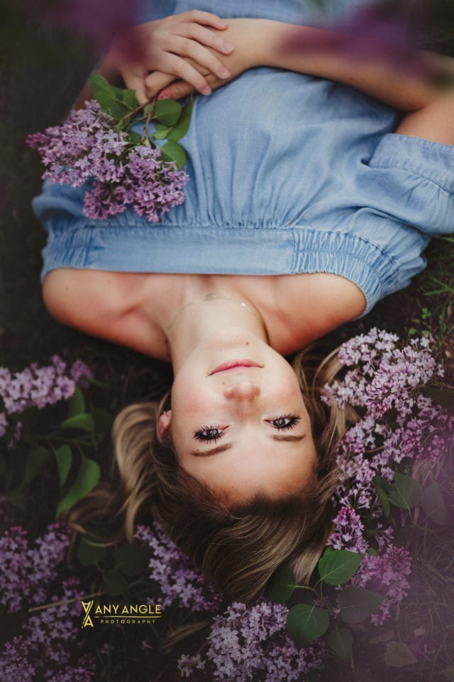 high school senior girl in blue dress laying down on her back on pile of lilac blossoms