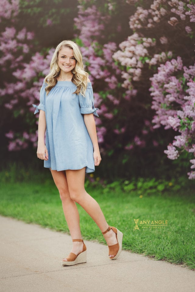 blonde high school senior girl in blue dress standing in front of tall purple lilac bushes smiling
