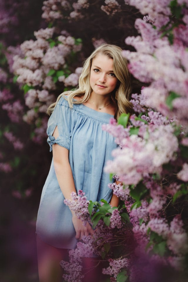 high school senior girl in blue dress standing in front of tall purple lilac bushes