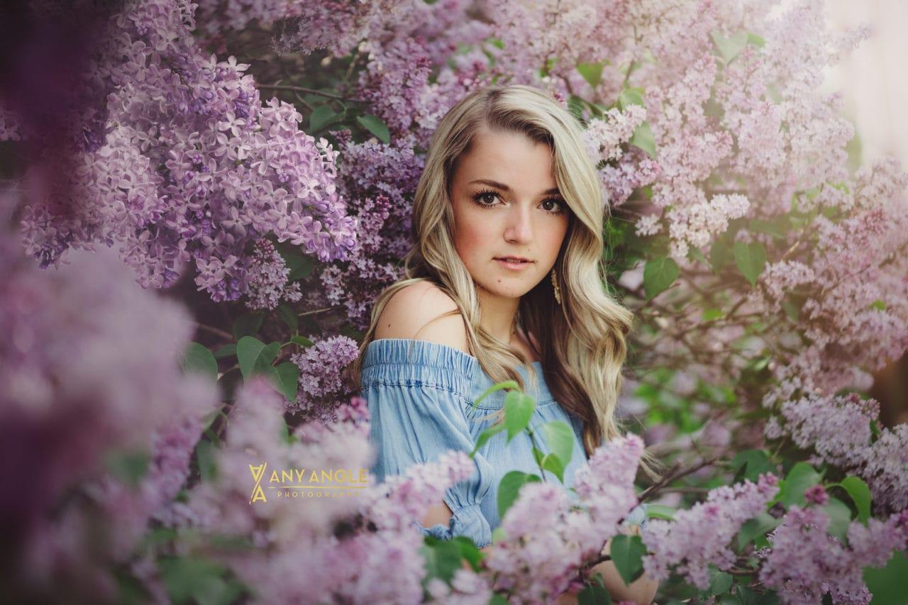 blonde high school senior girl in blue dress standing in purple lilac bush