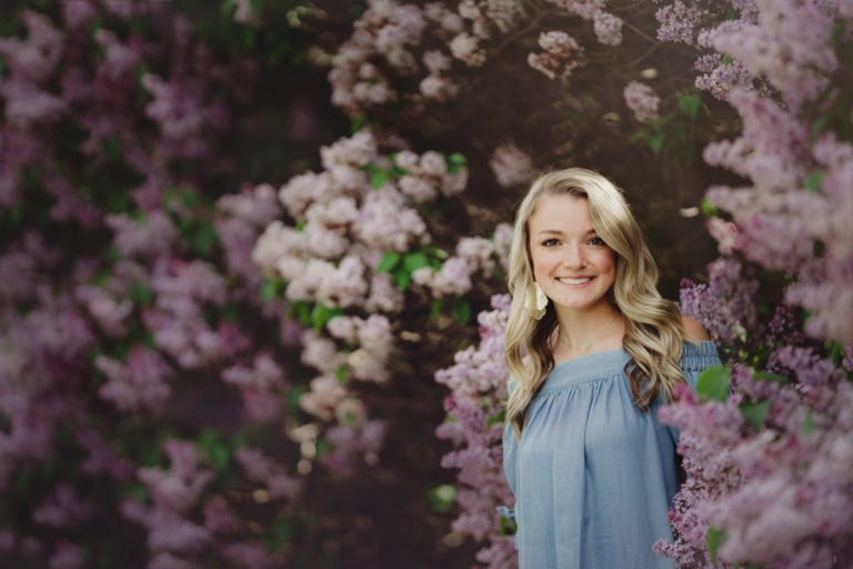 high school senior girl dressed in blue in front of lilac bushes
