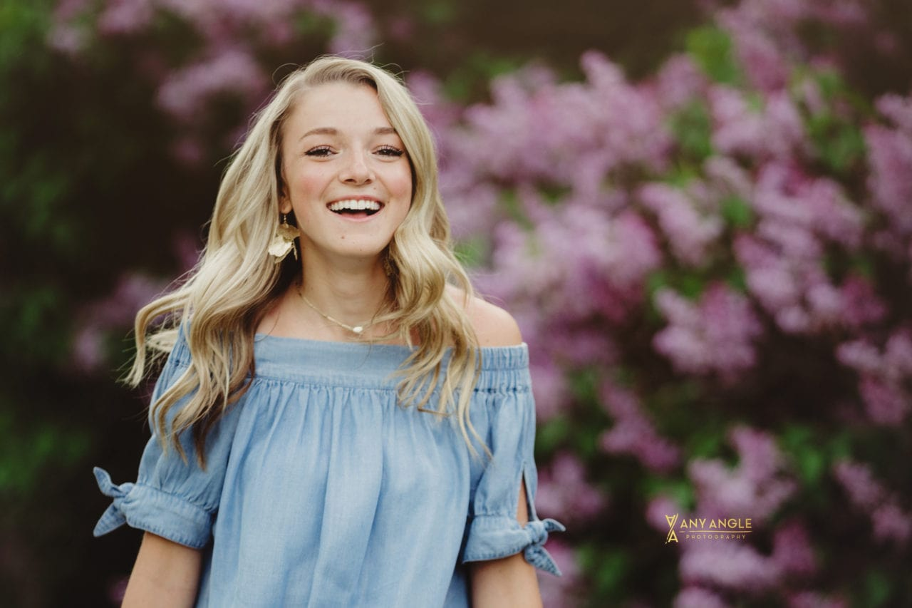 laughing high school senior girl dressed in blue in front of lilac bushes